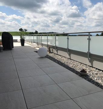 Terrasse mit Geländer aus Glas und Chromstahl mit Sicht auf dem See
