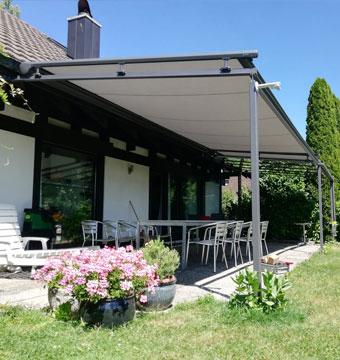 Terrasse mit Vordach mit schöner Wiese und Blumenwasen.